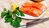 Appetizing raw salmon fillet with lemon and greens