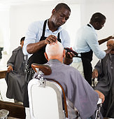 African hairdresser cutting with clipper