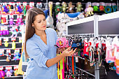 Positive young woman choosing pretty clothes for dog in pet shop