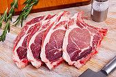 Raw pork chops on rib with herbs