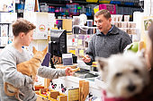 People with dogs shopping in pets shop