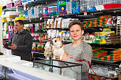 Glad man with son and dog buying pet supplies