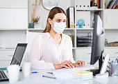 Female office worker in medical mask is having productive day at work in office
