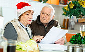 Aged family trying to pay utility bills before new year dinner