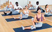 Young women and men exercising Hatha yoga poses in studio