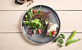 Jerked duck, smoked cream cheese and garlic ciabatta salad in gray plate top view