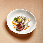 Rack of lamb in white deep plate close-up