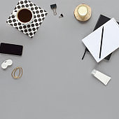 Home office desk. Workspace with phone, pen, candle, coffee mug, black diary on grey background. Flat lay, top view. Fashion blog look. Add your text.