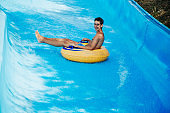 Cheerful teenager having fun sliding in water park