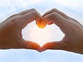 Kid hands making heart shape with blue sky and sunlight as background