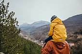Father carrying son on shoulders at top of the mountain