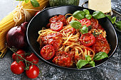 Tasty appetizing classic italian spaghetti pasta with tomato sauce, cheese parmesan and basil and ingredients