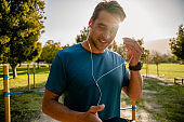 Young male athlete with smartwatch wearing ear phones listening to music on smartphone while exercising in outdoor park