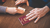 Male and female hands on table exchange Italian passport and money - concept of illegal immigration, sale of fake passports, sham (fake) marriage