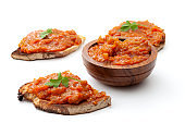 Traditional food from Romania concept with vegetable spread (Romanian: zacusca) on one slices of toast bread and wood bowl isolated on white background