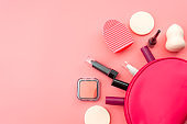 Fashion, beautician pouch and make up artist tool set conceptual idea with border made of essential beauty products spilling from a open makeup bag isolated pink color background with copy space