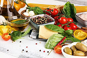 Italian food background with herbs and spices, vine tomatoes, basil, spaghetti, olives, parmesan, olive oil, garlic, peppercorns and fresh rosemary