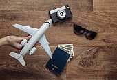 Travel flat lay composition. Hand holding plane figurine, camera, passport with dollar bills, sunglasses on wooden floor. Rest, vacation. Top view