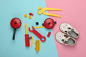 flat lay composition of children's sandals and toys on a blue-pink pastel background. Top view