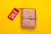 Fashionable leather wallet with red sale tag on yellow background. Top view. Discount. Shopping. Minimalism