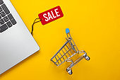 Laptop with a red sale tag, shopping trolley on yellow background. Big Sale, discounts, online shopping. Top view