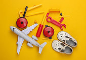 flat lay composition of children's sandals and toys on yellow background. Top view