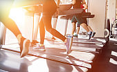 Group of people running on a treadmill. Cardio training for weight loss in the gym.