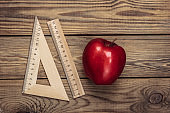 Back to school. Apple with rulers on a wooden table. Top view
