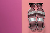 Creative summer beach flat lay. Leather women's sandals, sunglasses on colored background. Top view