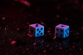 Dice in blue-red neon light on a dark background with drops of water