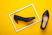 Women's classic high-heeled shoes on yellow background with a white frame. Fashion shot. Creative flat lay. Top view. Minimalism