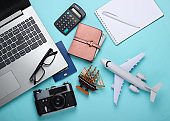 Travel concept. Calculation of the cost of vacation. Laptop, plane figurine, ship, calculator and traveler accessories on blue background. Top view. Flat lay