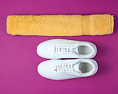 Training concept. Sport shoes, towel on a purple background. Top view