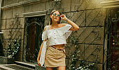 Street fashion. Fashionable stylish woman in trendy clothes and sunglasses posing outdoors against the background of old architecture