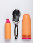 Shampoo bottles, hair conditioner, hair brushes on white background. Hair care. Hygiene. Beauty flat lay