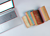 Modern laptop and many old books on a gray background. Old and new sources of information. Glitch effect. Top view