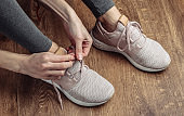 Fitness, sport concept. Woman tying shoelaces of sports shoes for running while sitting on the floor.