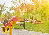 Attractive athletic girl doing exercises on exercise machines on the sports ground outdoors