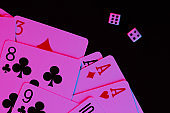 Playing cards with dice in neon blue-pink light on a black background. Game addiction. Poker