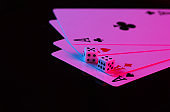 Playing cards of four aces with dice in neon blue-pink light on a black background. Game addiction. Poker
