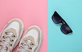 Fashionable sneakers with sunglasses on pink blue pastel background. Top view. Minimalism