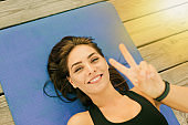 Young cheerful sport woman lies on mat and shows V symbol. Top view portrait