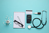 Doctoral supplies and tools, calculator on blue background. Economic calculation of the effectiveness of healthcare and medicine. Doctor workspace