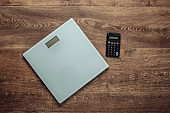The concept of weight loss, fitness. Calorie Counting. Floor heights, calculator on wooden floor. Top view