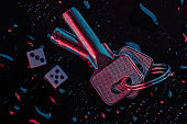 Dice and keys in blue-red neon light on a dark background with water drops. Game addiction