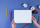 Woman going to draw with colored pencils on blue background with crumpled paper balls. Top view