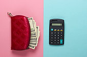 Red purse with hundred dollar bills and a calculator on a blue-pink pastel background. Counting the cost of purchases. Top view