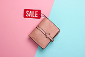 Fashionable leather wallet with red sale tag on pink blue background. Top view. Discount. Minimalism