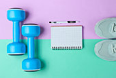 Fitness concept, workout plan. Plastic blue dumbbells, sport shoes, notepad on pastel background. Top view. Flat lay