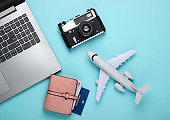Online ticket booking. Choosing a travel destination. Laptop and airplane figurine, travel accessories on a blue pastel background. Tourism, rest, vacation. Top view